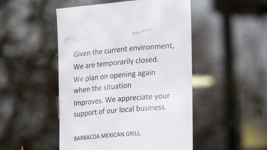 Salt Lake City, Utah, March 2020.  A sign on the front door of a closed business, Barbacoa Mexican Grill, because of social distancing due to the Corona Virus, or COVID-19.