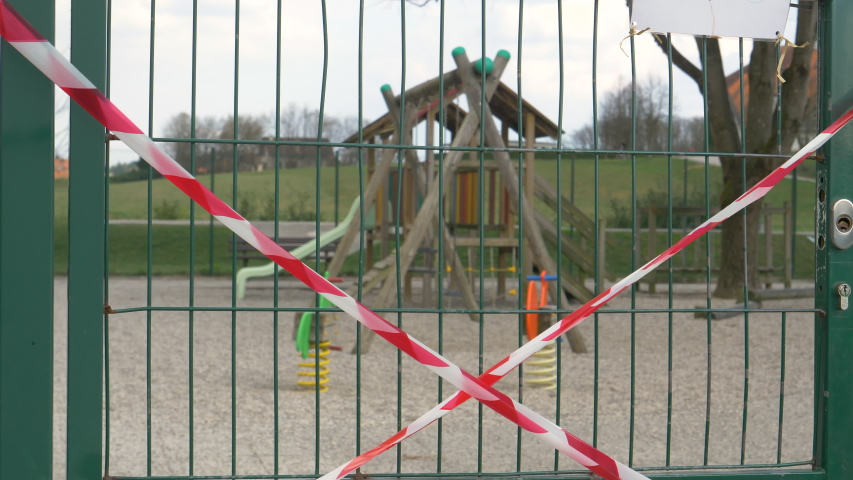 CLOSE UP, DOF: Red and white tape forbidding people to enter the kindergarten playground flutters in the wind. Entrance to a playground is locked and taped up due to the coronavirus epidemic in Europe Royalty-Free Stock Footage #1049202274