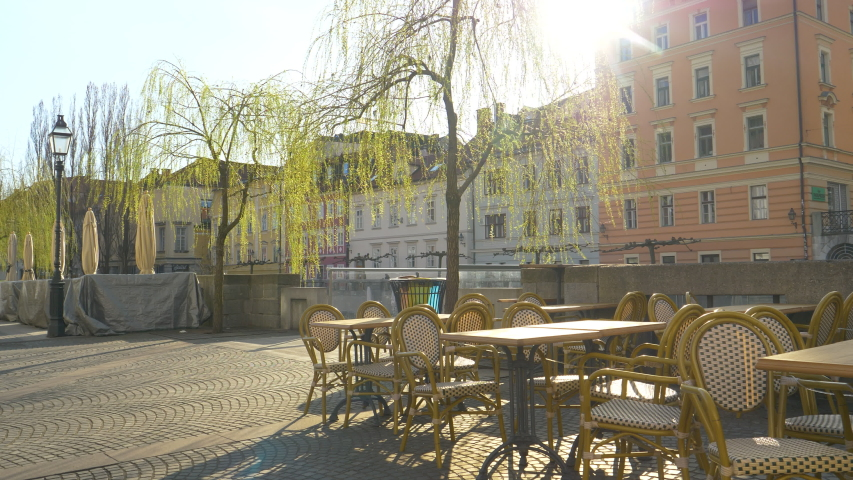 Warm spring sun rays shine on empty chairs and tables of a bar closed due to covid-19. Dreary view of an empty tourist street in the old town of Ljubljana. No people in sunny city during quarantine.