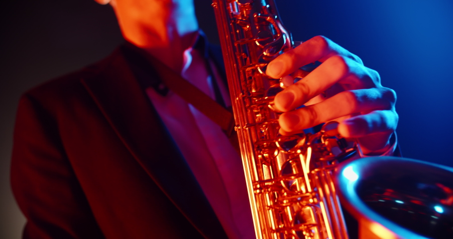 Cool saxophone player performing a solo on stage, spotted by red and blue light. Musician playing in jazz band - close up 4k footage | Shutterstock HD Video #1049208760