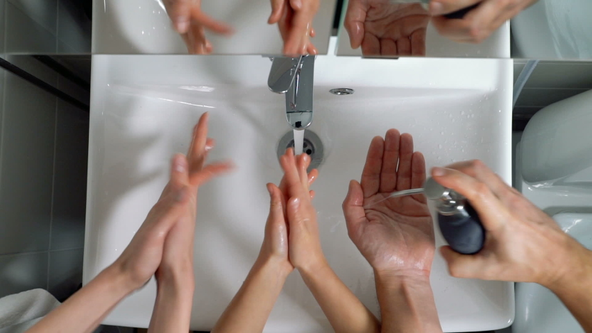 Family couple with child washing hands in bathroom at home, Coronavirus hand washing for clean hands hygiene. Top view | Shutterstock HD Video #1049209471