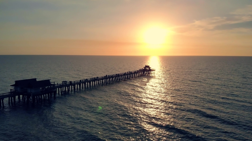 Silhouette of a pier over the water at sunset. Naples Beach and Fishing Pier at Sunset, Florida. Small Pier in Calm Ocean with Sun Reflecting on Water. Sunset over the Pier. Beautiful Ocean Sunsets. | Shutterstock HD Video #1049209645