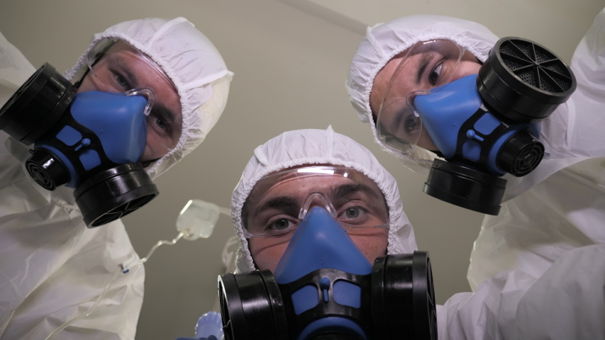 Emergency medical service. Doctors in protective suits carry the patient. Royalty-Free Stock Footage #1049212339