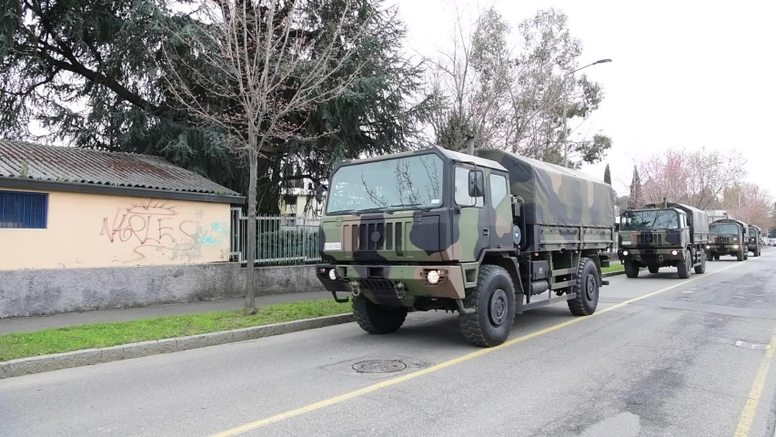 Bergamo, Italy - March 26, 2020: a convoy  of military trucks transport coffins of deceased people, mostly died from coronavirus covid-19, from the cemetery to a crematorium outside the city