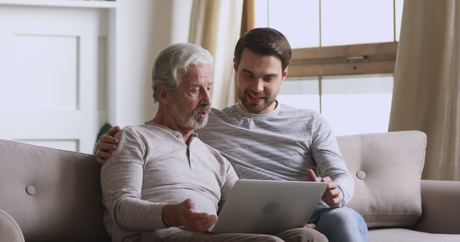 Handsome young man cuddling happy elderly mature father, helping teaching using computer applications, sitting together in living room. Middle aged dad discussing media news with grown up son indoors. #1049214823