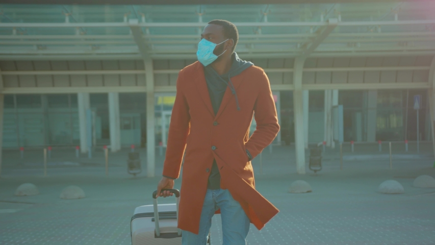 African American man wearing Protective Face Mask to avoid disease COVID-19 coronavirus infection with suitcase near airport pandemic disease virus male tourist epidemic air health illness slow motion Royalty-Free Stock Footage #1049217085