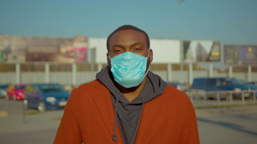 African American man wearing Protective Face Mask to avoid disease COVID-19 coronavirus infection look at camera near airport pandemic disease virus male tourist epidemic air health illness slow #1049217088