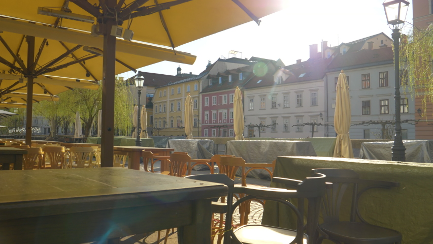 LENS FLARE: Golden spring sunbeams shine on terrace of a restaurant, closed as a result of a coronavirus quarantine. Riverside bars and restaurants in Ljubljana are closed due to covid-19 epidemic. Royalty-Free Stock Footage #1049230420
