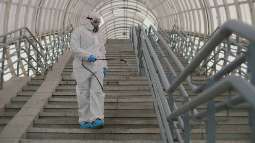 Virologist in protective suit disinfects surface, sprays liquid chemicals on handrails. Sanitary measures against coronavirus in public place Covid-19 coronavirus spreading prevention