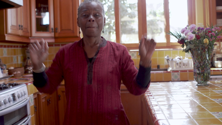 Smiling happy mature black woman dancing and celebrating life and success in her kitchen