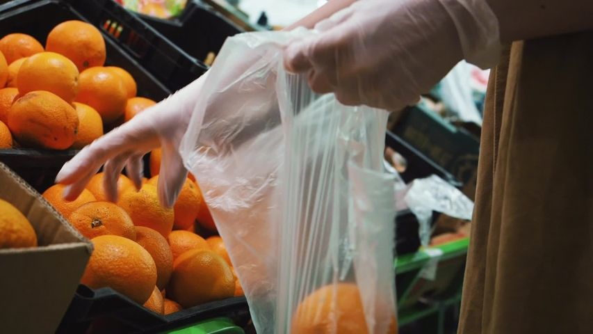 Woman selects fresh oranges Vitamin C in latex gloves to boost immunity in a grocery store. Close up | Shutterstock HD Video #1049263666