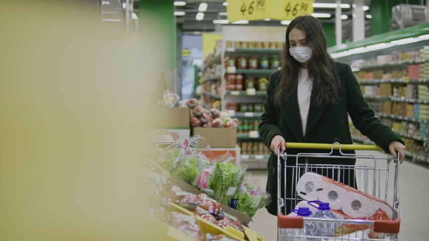 Young woman in protective medical mask buys food and hygiene items at supermarket during covid-19 coronavirus epidemic. Woman stocks up on food and toilet paper during quarantine and self-isolation