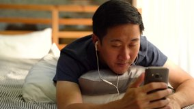 Portrait of happy 30s Asian man in casual clothing making facetime video calling with smartphone at home, waving at people on phone screen. Using conferencing meeting online app, social distancing