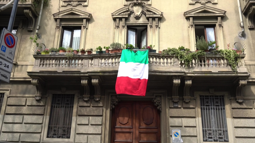 Europe, Italy , Milan - Flag of Italy hanging on the balcony of a house during n-cov19 Coronavirus epidemic emergency - Italian flash mob Royalty-Free Stock Footage #1049306506