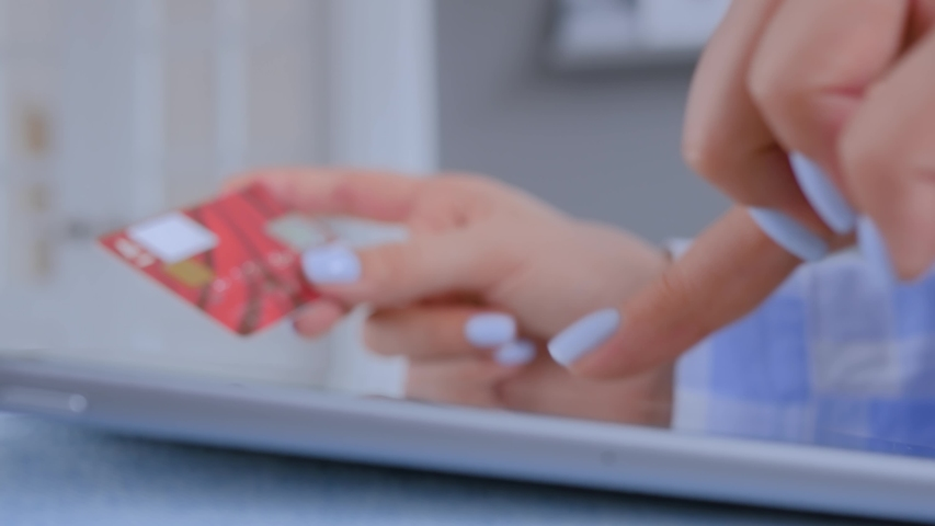Close up view - woman using tablet device, holding credit card, buying goods or ordering online. E-commerce, online shopping, sale, consumerism, electronic payment, technology concept