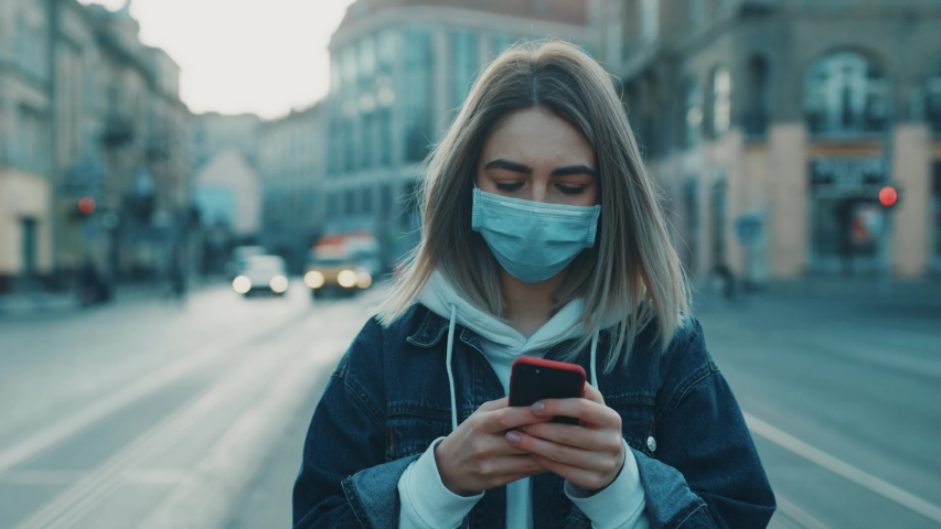 Young blonde woman in protective medical mask walks down to the street uses phone texts scrolls surfs the internet search news covid19 coronavirus virus protection pandemic city slow motion close up | Shutterstock HD Video #1049314351