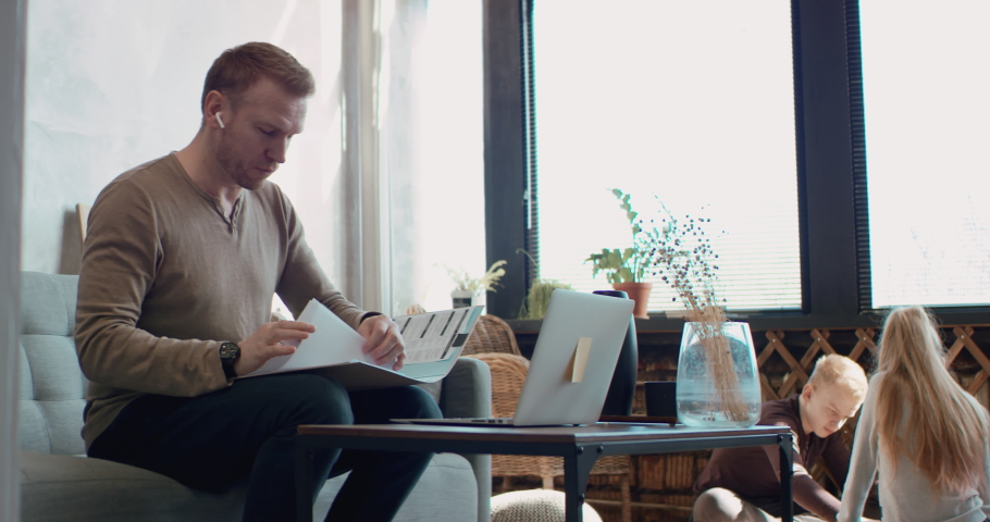 Mid 30s Caucasian male working from home, having a video call with colleagues. Family playing in the background. Stay home, quarantine remote work. Shot on RED Dragon Royalty-Free Stock Footage #1049328991