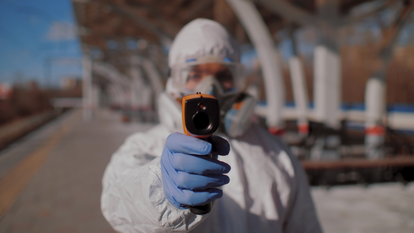 Medical worker wearing protective suit, goggles and respirator checks temperature of people. Controlling disease to prevent Covid-19 coronavirus pandemic, epidemic, close up, pov | Shutterstock HD Video #1049350315