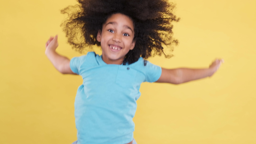 Happy and Joyful Little 5 years old Kid Jumping on yellow Background. She Smiling, Laughing and Feel Well. Playful Preschool Kid Have Fun Indoor. Rejoicing, Positive Feelings. Slow motion shoot.