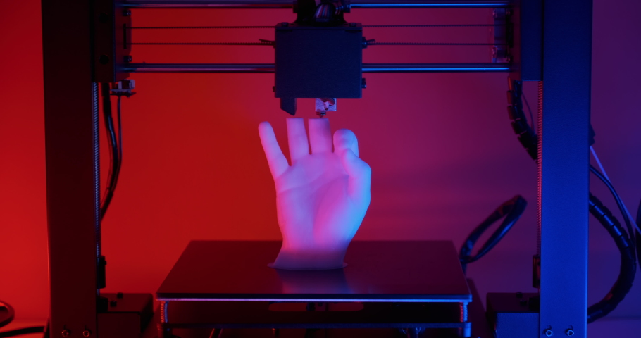 3D printer prints model hands fingers ok sign made white plastic closeup red blue neon light. Clear movements of print head and printer working platform. Potential modern 3D printing technology | Shutterstock HD Video #1049363671