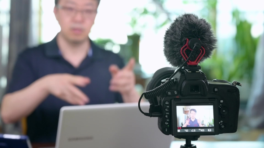 Online lecture concept. Asian middle-aged man giving online lectures at home. Blur background.