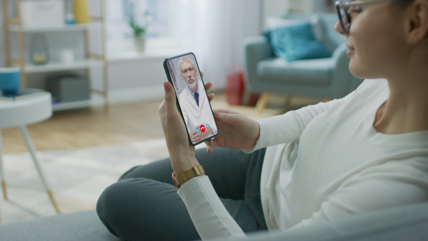 Young Girl Sick at Home Using Smartphone to Talk to Her Doctor via Video Conference Medical App. Beautiful Woman Checks Possible Symptoms with Professional Physician, Using Online Video Chat Royalty-Free Stock Footage #1049374144