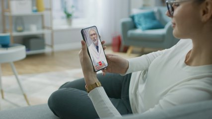 Young Girl Sick at Home Using Smartphone to Talk to Her Doctor via Video Conference Medical App. Beautiful Woman Checks Possible Symptoms with Professional Physician, Using Online Video Chat