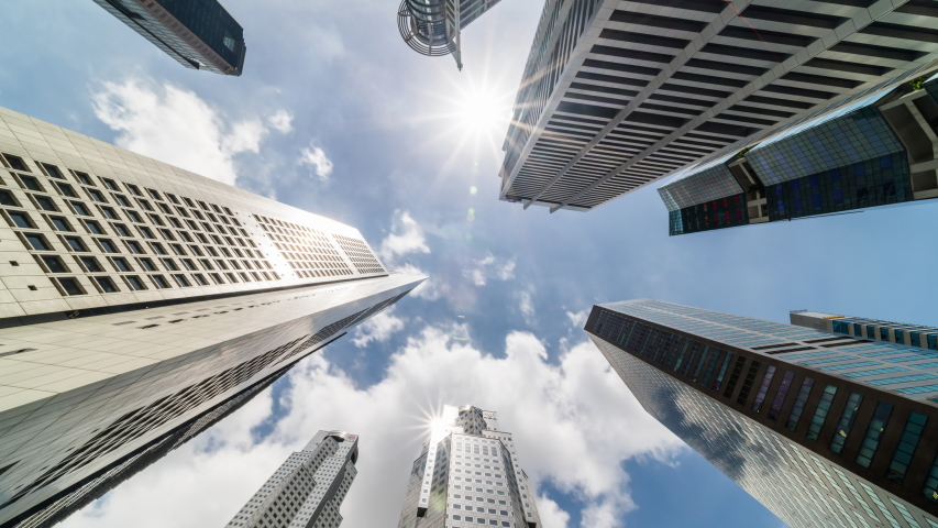 Time-lapse of skyscraper buildings in business district, Singapore city. Cloud on sunny day sky. Low angle view, zoom out. Asia financial economy, merger & acquisition, or modern architecture concept Royalty-Free Stock Footage #1049381404