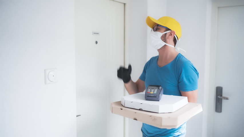 Deliveryman with protective medical mask holding pizza box and POS wireless terminal for card paying - days of viruses and pandemic, food delivery to your home and safety hygiene measures. | Shutterstock HD Video #1049383357
