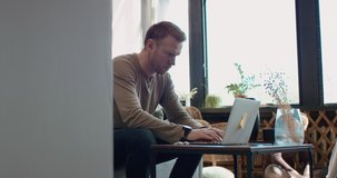 Mid 30s Caucasian male working from home, checking documents. Kids playing in the background. Stay home, quarantine remote work. Shot on RED Dragon