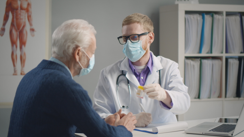 Elderly patient having flu visiting doctor wearing medical mask and having medicine prescribed against influenza. Physician seeing patients in facial masks to protect from covid-19 epidemic | Shutterstock HD Video #1049385913