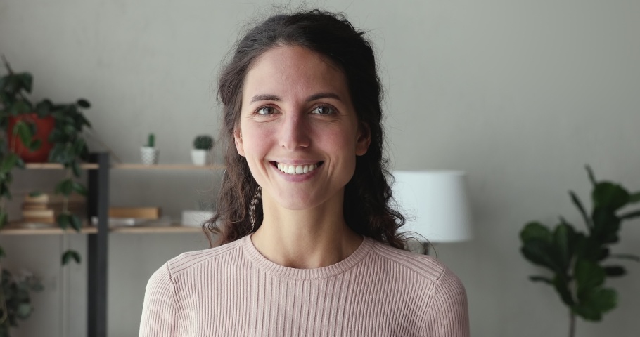 Confident smiling young adult european woman looking at camera standing at home office. Happy millennial casual professional lady with white teeth pretty face posing for close up portrait indoors.
