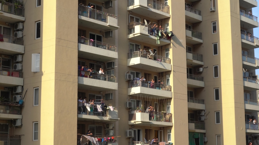 Gurgaon, Delhi, India - circa 2020 : Locked on shot of India families men, women, children clapping cheering form their balconies as they celebrate the contribution of essential workers like doctors