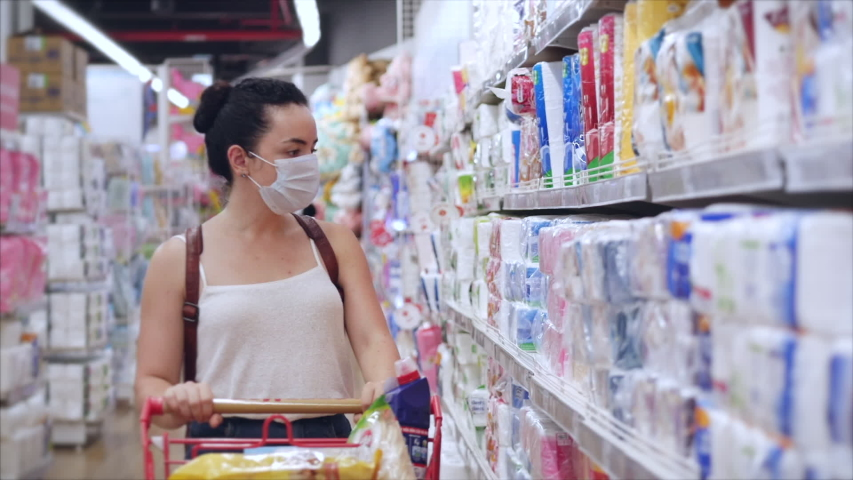 Young woman in a mask from a coronavirus epidemic buys toilet paper in a supermarket, where people panicky buy everything. Corontin, isolation of people. | Shutterstock HD Video #1049402866