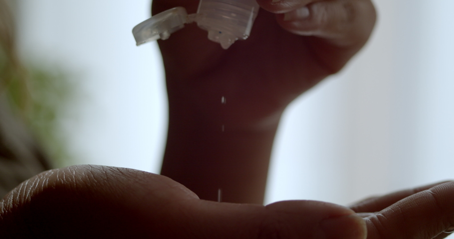 Very close drop from hand sanitizer as woman then lathers her hands to prevent the transmission of pathogens protecting herself from the coronavirus outbreak and pandemic   Shutterstock HD Video #1049402998