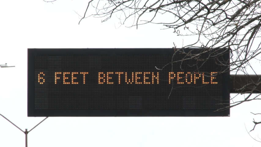 "Road sign close up reading ""Keep your distace, 6 feet between people"" as the corona virus sweeps across the country. 