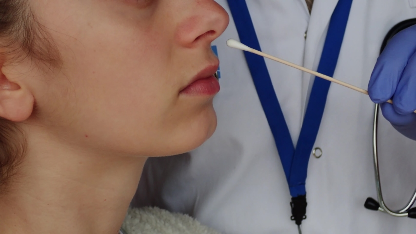 Quick test for suspected coronavirus diagnosis.  Physician taking a nasofaringeal sample of a young woman, with a cotton swab. Covid19 screening. Child. Royalty-Free Stock Footage #1049411041