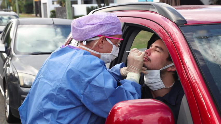 A doctor in a protective suit taking a nasal swab from a driver to test for possible coronavirus infection Royalty-Free Stock Footage #1049411785