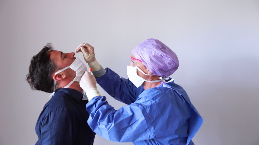 A doctor in a protective suit taking a nasal swab from a person to test for possible coronavirus infection Royalty-Free Stock Footage #1049411812
