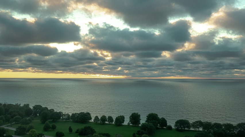 Aerial timelapse of a bright yellow sun shines its rays through openings in white fluffy clouds hovering over Lake Michigan as it rises through the sky.