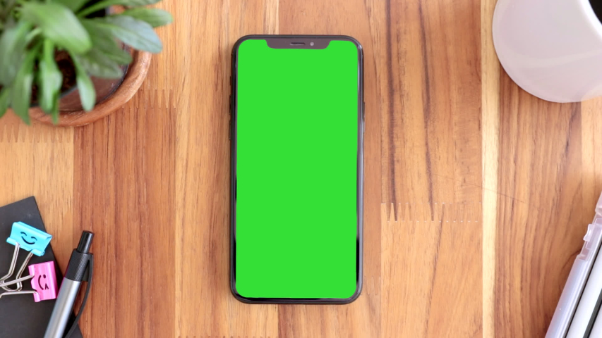 Thailand, Roi-rd - March30, 2020 : Smart phone place on table wood with green screen, Close-up the cell phone is on the brown desktop with chroma key, Green screen telephone, slider and top view.