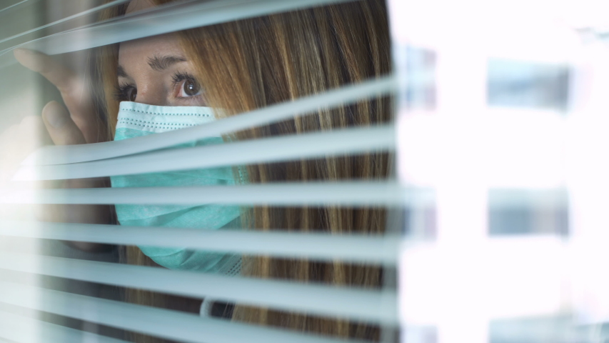 Sad young woman wearing medical protection mask looking out the window through the blinds at home. Home quarantine coronavirus. Social distancing, self isolation. Royalty-Free Stock Footage #1049431726
