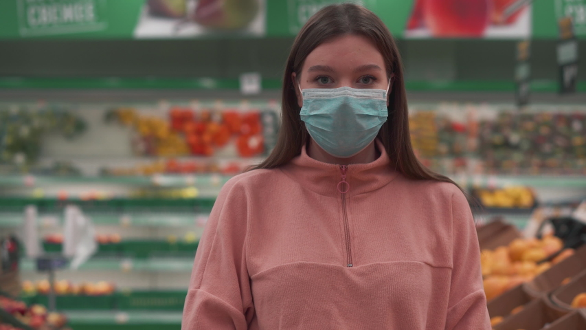 Young beautiful girl straightens a medical mask in a store. Shopping center emptied into coronavirus. Protective gloves against the spread and transmission of infection. | Shutterstock HD Video #1049435380