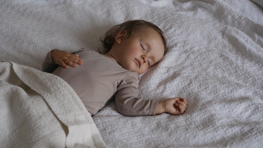 Peaceful  baby girl sleeping on  bed in a room. Soft focus. Sleeping baby concept. One year-old babygirl sleeps at home. Mom covers her daughter with a blanket
