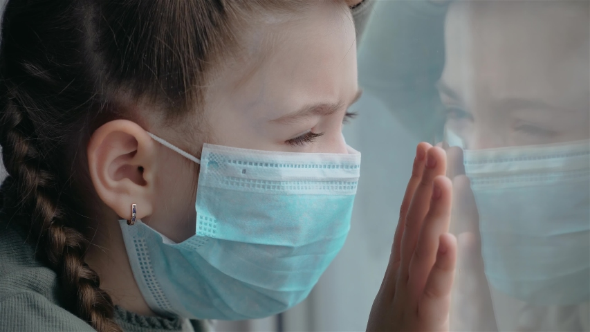 Portrait of little girl in medical mask looks sadly at her reflection in window during worldwide virus epidemic. Stop COVID-19 infection Royalty-Free Stock Footage #1049438449