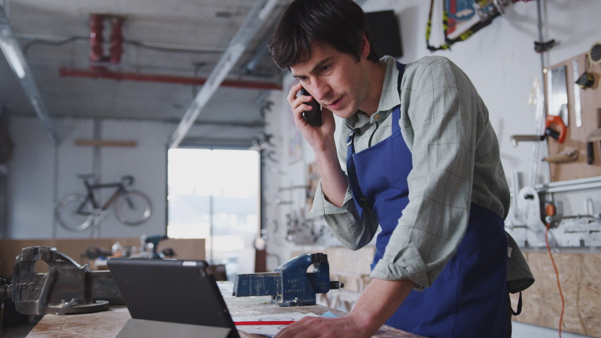 Male business owner in workshop using digital tablet and making call on mobile phone - shot in slow motion Royalty-Free Stock Footage #1049442229