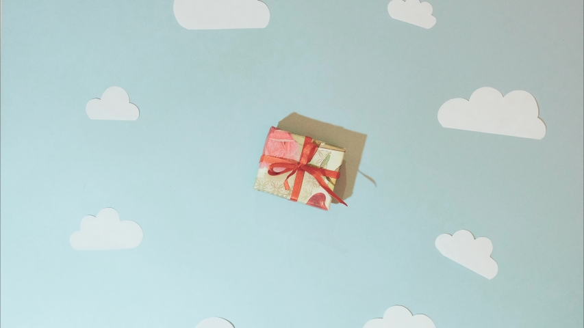 Stop motion of unboxing gift. Paper plane flying over clouds on blue background. Stop motion. Footage video of unboxing. Gift. Process of unboxing