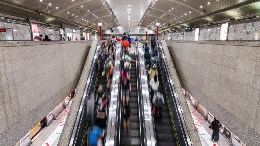 Singapore, Singapore - Feb 6, 2020: Asian people walk and use escalator at MRT subway underground station. Public transportation, Asia everyday city life, or commuter urban lifestyle concept. Tilt up