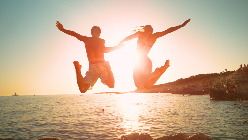 SLOW MOTION, LOW ANGLE, LENS FLARE: Cheerful couple on summer vacation jumps into the ocean at sunrise. Golden evening sun rays shine on young man holding girlfriend's hand as they jump in the water.