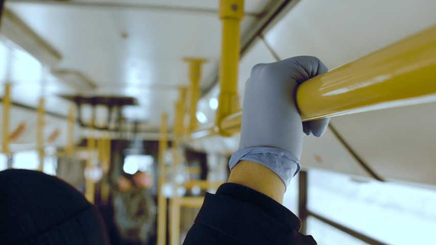 A man rides in a public transport bus and holding on to a handrail in his protective medical glove. Coronavirus covid-19 infection and epidemic protection concept. Pandemic. Closeup shot Royalty-Free Stock Footage #1049467294